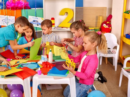 Kids holding colored paper on table in kindergarten .