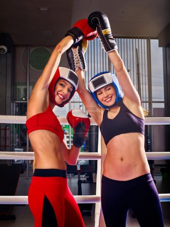 Portrait of two sport girl boxing on ring.