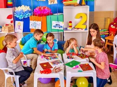 Photo for Group clever children with young beautiful teacher mold from plasticine in primary school. Children school education. - Royalty Free Image