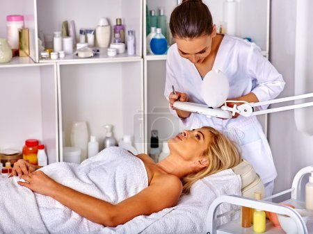 Woman middle-aged lying in spa salon. Tweezing eyebrow beautician.