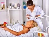 Žena středního věku, ležící ve spa salonu. Pinzetové obočí kosmetička
