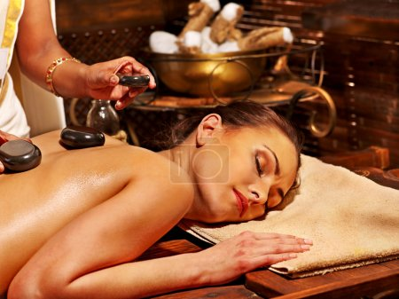 Woman having stone massage.