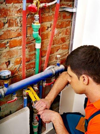Photo pour Homme constructeur système de chauffage de fixation avec outil spécial . - image libre de droit