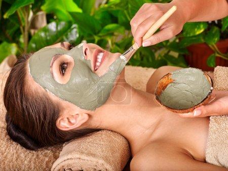 Photo pour Femme avec masque facial en argile dans un spa de beauté. Serviette sous le cou - image libre de droit