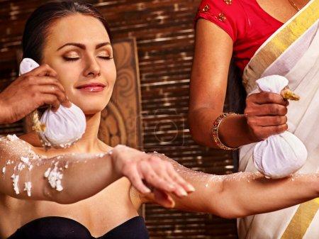 Photo pour Femme ayant un massage ayurvédique avec poche de riz. Les mains tendues - image libre de droit