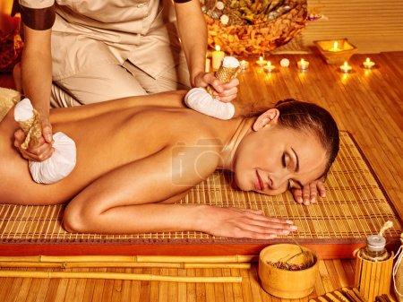 Foto de Mujer recibiendo masaje de bolas de hierbas a la luz de las velas en el spa. Los ojos están cerca. . - Imagen libre de derechos