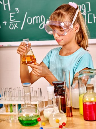 Photo for Child holding flask in chemistry class. Mask on face. - Royalty Free Image