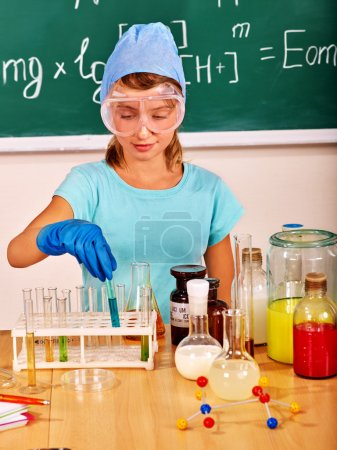 Photo for Child holding flask in chemistry class. - Royalty Free Image