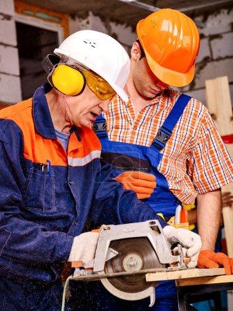 Photo pour Deux hommes constructeurs avec scie circulaire. Mur de briques en arrière-plan - image libre de droit