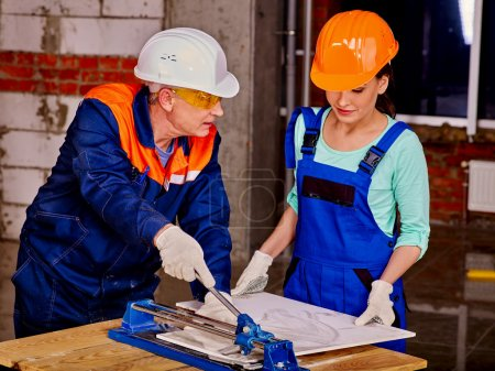 people builder cutting ceramic tile.