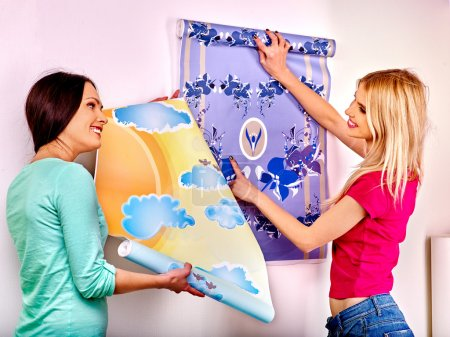 Foto de Happy two women glues wallpapers at home indoor. - Imagen libre de derechos
