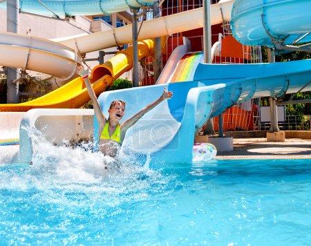 Happy child girl in bikini sliding water park....