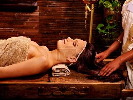 Photo pour Woman having facial  ayurveda spa treatment on wooden massage table. - image libre de droit