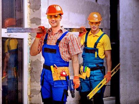 Happy strong men in builder uniform....