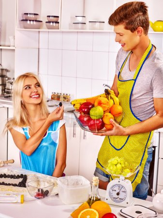 Photo for Young happy family blond woman and strong man cooks at kitchen. - Royalty Free Image