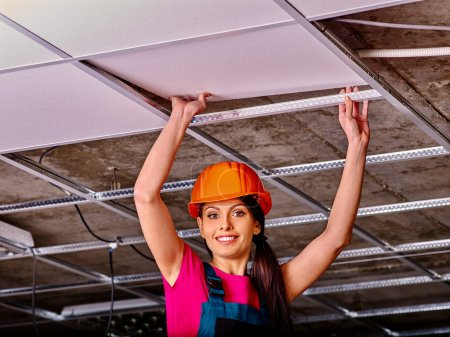 Woman installing suspended ceiling