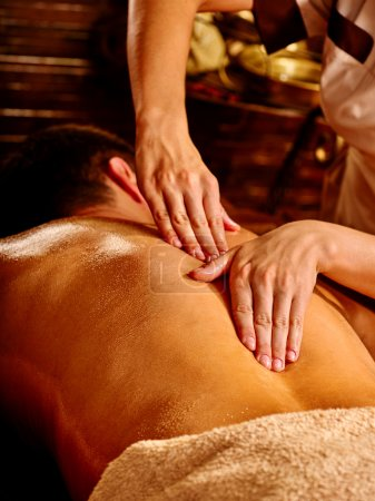 Man having Ayurvedic spa treatment.