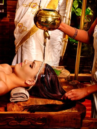 Woman having head Ayurvedic spa treatment.