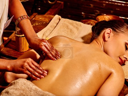 Young woman having oil Ayurveda spa treatment. Back.