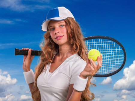 Girl  holding tennis  racket and ball on blue sky with clouds.