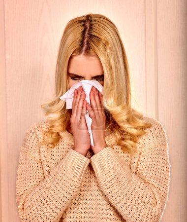 Young woman wisneezes in handkerchief having  cold.