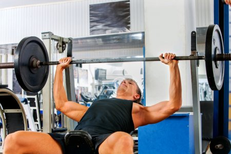 Man working his arms and chest at gym.