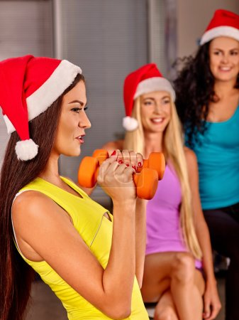 Photo for Group people  wearing Santa hat holding dumbbells in sport gym. Sport Christmas concept - Royalty Free Image