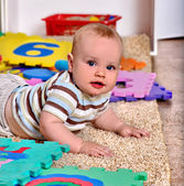 Kid baby boy plying with puzzle toy on floor.