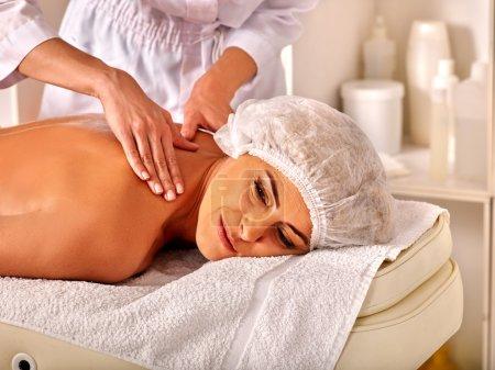 Photo pour Femme d'âge mûr portant chapeau cosmétiques dans le salon spa recevoir massage par esthéticienne - image libre de droit