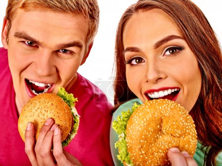Photo for Young man and woman biting big hamburger. Fastfood concept. Isolated - Royalty Free Image