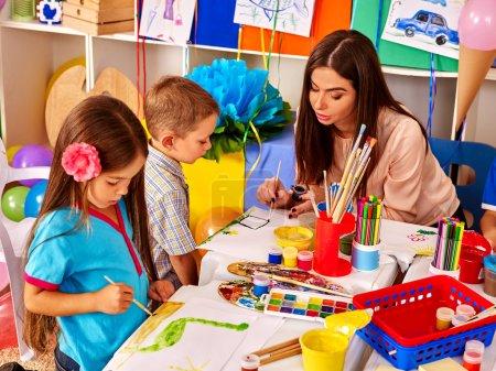 Photo pour Enfants avec professeur femme peinture sur papier à table à la maternelle. Personnes de groupe - image libre de droit