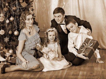 Foto de Familia feliz con los niños que recibieron regalos bajo el árbol de Navidad. blanco y negro retro - Imagen libre de derechos