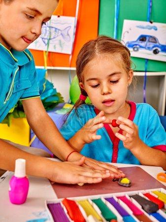 Photo pour Groupe d'enfants garçon et fille de moule de pâte à modeler en maternelle - image libre de droit