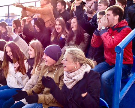 Sport fans clapping and singing on tribunes