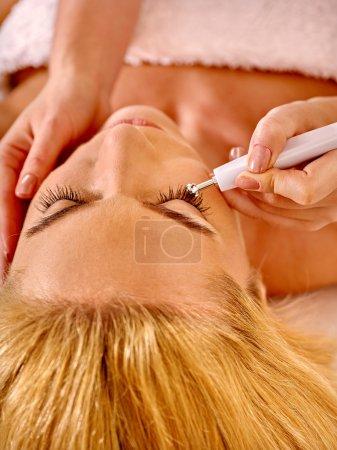 Woman receiving electric facial massage