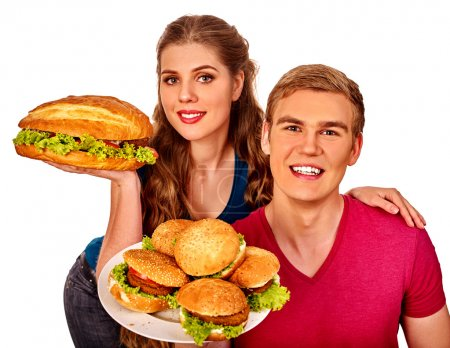 Photo for Young couple man and woman holding a lot of hamburgers. Fast food concept. Isolated - Royalty Free Image