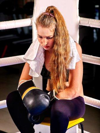 Girl wearing sport gloves sitting in corner of boxing ring.