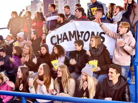 Sport fans holding champion banner on tribunes.
