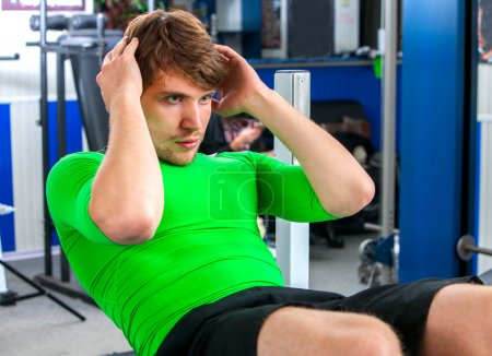 Man in green clothing working his abdominal crunches on bench in gym