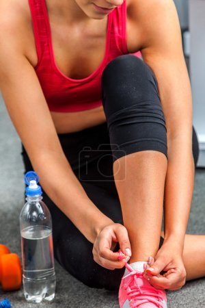 Fit woman sitting on floor