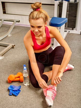 Woman sitting on floor at gym