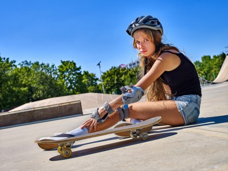 Sport girl with injury near her skateboard outdoor.