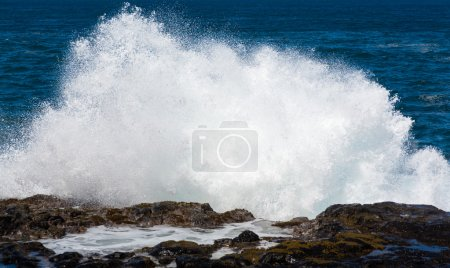 Raging sea flows over lave rocks on shore line