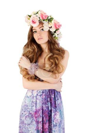 Beautiful women supermodel in wreath of flowers close up portrait.