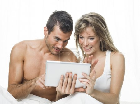 attractive couple watching things in a tablet