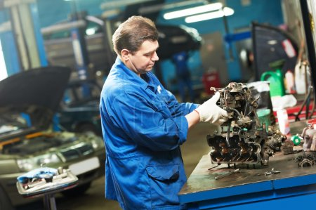 auto mechanic at work with engine