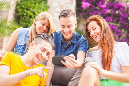 Group of teenagers laughing and looking at a smart phone