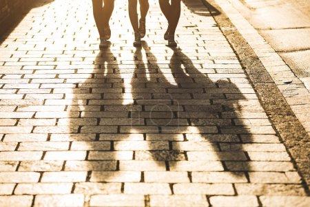 Shadows of three girls walking on a sidewalk in the city