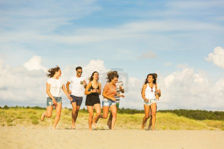 Multiracial group of friends running on the beach