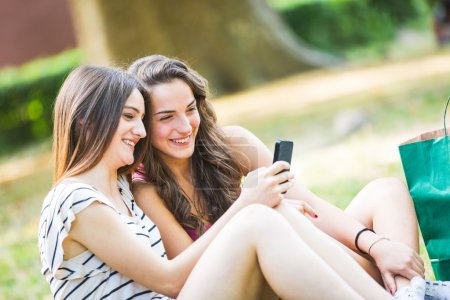 Photo for Two girls looking at smart phone at park. They are happy and smiling, sitting on the grass with shopping bags on background. Friendship and lifestyle concepts. - Royalty Free Image